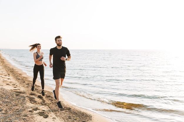 Sportief jong koppel samen joggen op een strand