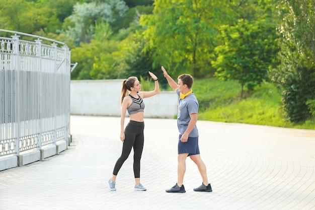 Sportief jong stel dat elkaar buitenshuis high-five geeft
