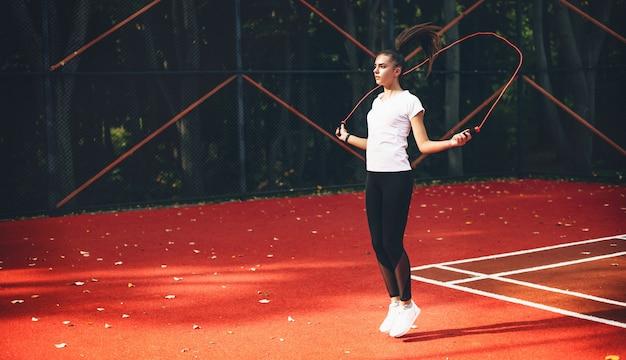 Sportief kaukasisch meisje met behulp van een springtouw op een rood tennisstadion in een zonnige zomerochtend