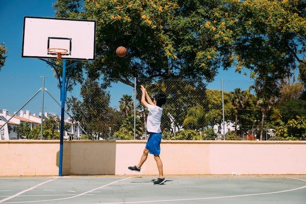 Sportief mannetje dat bal werpt in hoepel op stedelijke achtergrond