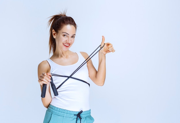 Sportief meisje dat een blauw springtouw vasthoudt en duim laat zien.