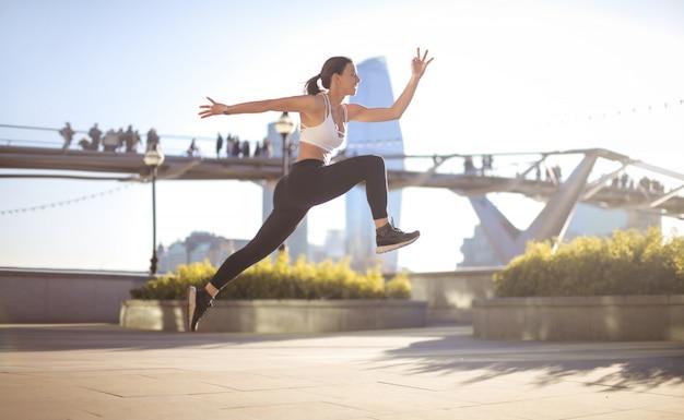 Sportief meisje dat hoog in de straat springt