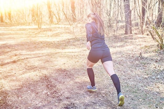 Sportief meisje dat in het bos loopt