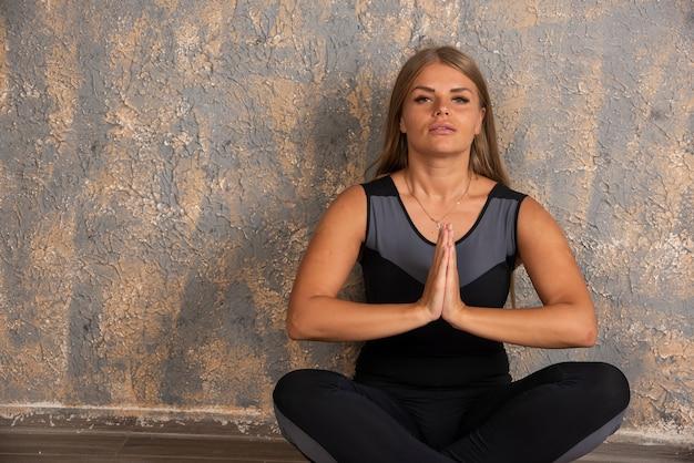 Sportief meisje dat meditatie doet en in lotusbloempositie zit.