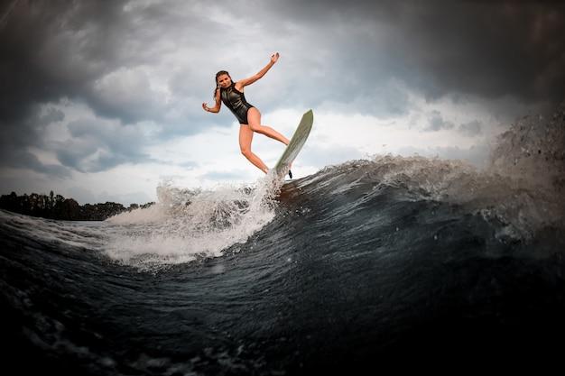 Sportief meisje dat op wakeboard op de rivier op de achtergrond van bomen springt die handen springen