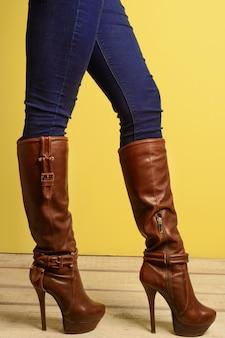 Sportief meisje dat zich in bruine laarzen met hoge hakken en jeans bevindt