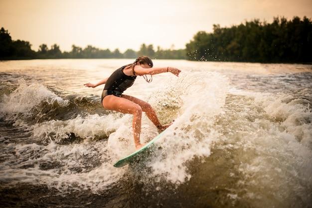Sportief meisje die een truc op wakeboard op de rivier in de zonsondergang maken