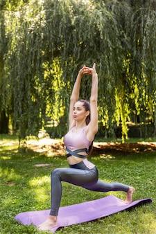 Sportief meisje die fysieke oefeningen op de yogamat doen in een park