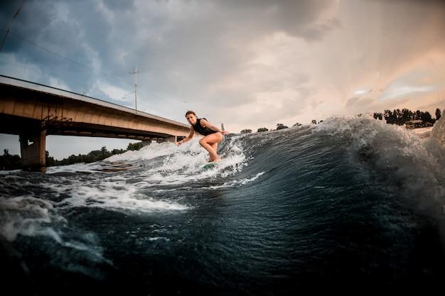 Sportief meisje die op wakeboard op de rivier op de achtergrond van de brug berijden