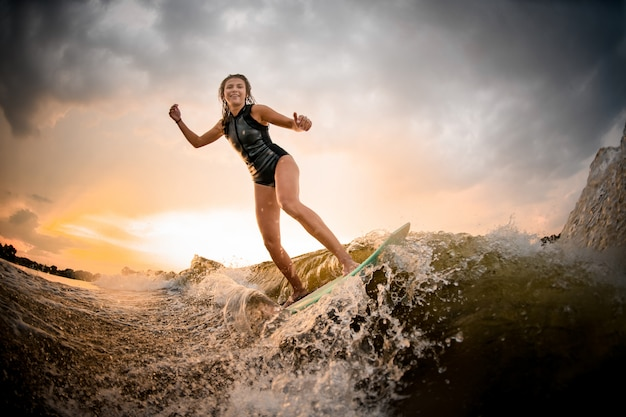 Sportief meisje die op wakeboard op de rivier op de golf op de buigende knieën berijden
