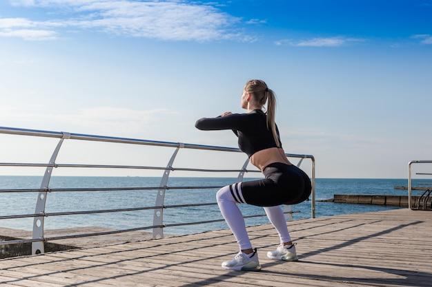 Sportief meisje doet squats in de buurt van de zee