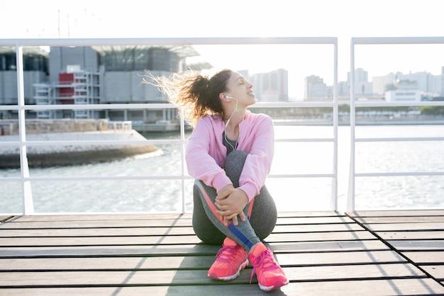 Sportief meisje geniet van luisteren naar muziek op kade