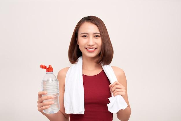 Sportief meisje met fles water en handdoek op haar schouders op licht Premium Foto