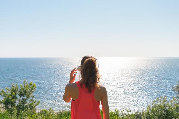 Sportief meisje met hoofdtelefoons en een rood mouwloos onderhemd die het overzees in de zomer bekijken