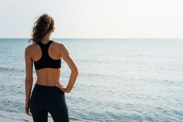 Sportief meisje met krullend haar in een sportenbustehouder die zich op het strand bevinden en het overzees in de ochtend bekijken