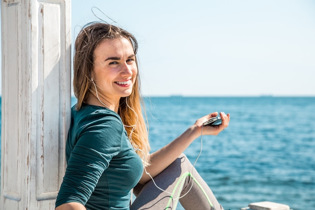 Sportief meisje op de pier met de telefoon