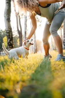 Sportief meisje speelt met hond in het park buiten in de zomer