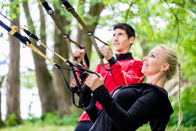 Sportief paar bij slingertrainer die geschiktheid doet
