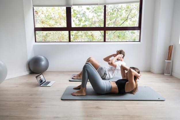 Sportief paar in sportkleding die oefening doet die laptop thuis gebruikt
