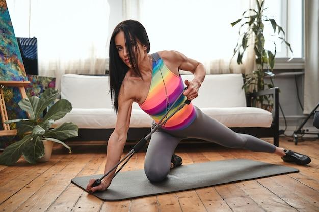Sportief portret van een sterke sportvrouw van middelbare leeftijd die aan het trainen is met behulp van rubberen elastische banden in een lichte kamer met een prachtig interieur.