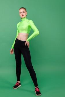 Sportief slank meisje in beenkappen op een groene ruimte