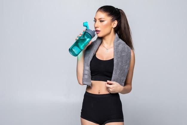Sportief spiervrouwen drinkwater, dat tegen witte muur wordt geïsoleerd