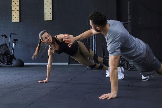 Sportief stel doet push-ups en geeft elkaar high five in de sportschool.