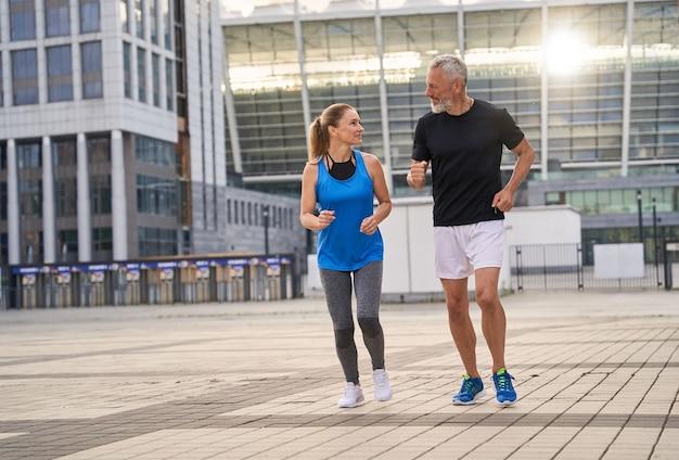 Sportief stel man en vrouw van middelbare leeftijd in sportkleding aan het chatten terwijl ze samen buiten joggen