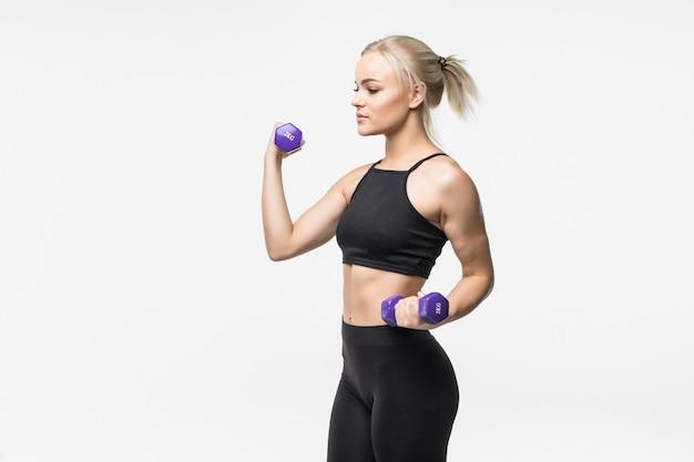 Sportief vrij blond jong meisje met fit gespierd lichaam werkt met halters in studio op wit