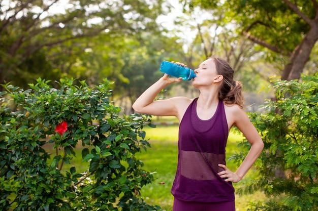 Sportief vrouwen drinkwater in park