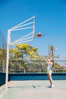 Sportief wijfje die bal werpen in hoepel op aardachtergrond
