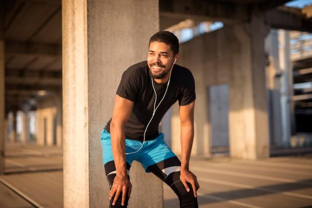 Sportieve aantrekkelijke man, luisteren naar muziek en glimlachend op training