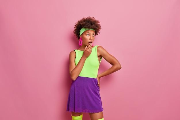 Sportieve afro-amerikaanse vrouw gekleed in heldere zomeroutfit, hoofdband, kijkt weg met wijd geopende mond, merkt vreemd schokkend ding op