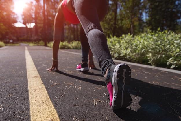Sportieve atleetvrouw op de startpositie op een lopende manier openlucht. zonsondergang of zonsopgang op de achtergrond.
