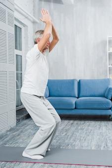 Sportieve bejaarde beoefenen van yoga binnenshuis