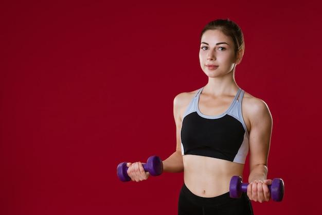 Sportieve blanke jonge vrouw in sportkleding met halters in haar hand op een rode muur