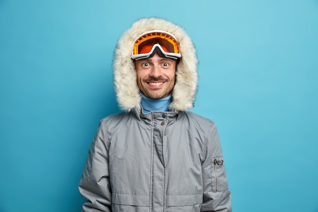 Sportieve blije man geniet van wintersport recreatie glimlacht graag draagt skibril en grijze jas.