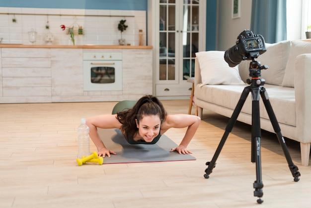 Sportieve blogger die opdrukoefeningen voor camera doet