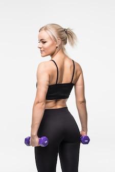 Sportieve blonde lachende jong meisje met fit gespierd lichaam werkt met halters in studio op wit