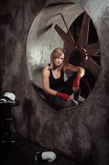 Sportieve blonde vrouw in boksverband en bokshandschoenen rond in een donkere studio die naar de camera kijkt