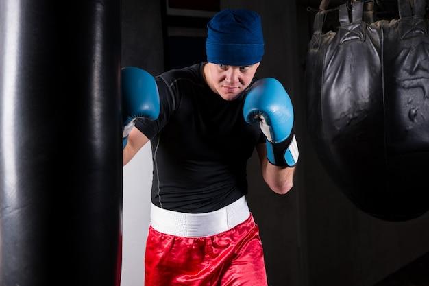 Sportieve bokser in bokshandschoenen training met bokszak boksen in een sportschool