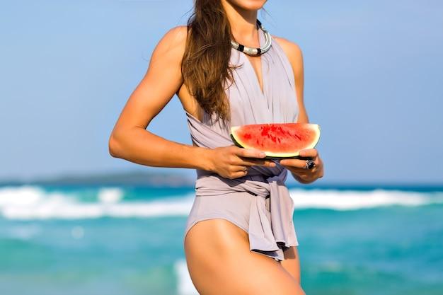 Sportieve brunette meisje in elegante zwembroek poseren voor zee. openluchtportret van slank langharig vrouwelijk model dat een plakje watermeloen houdt terwijl hij aan de kust staat.