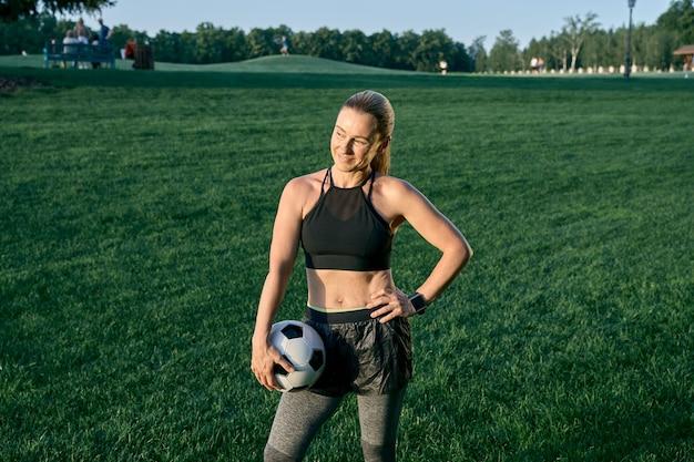 Sportieve dame atletische mooie vrouw van middelbare leeftijd voetballer die lacht en de bal vasthoudt terwijl