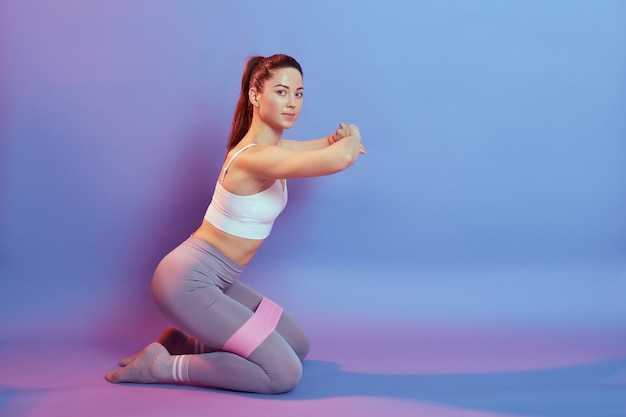 Sportieve donkerharige europese vrouw draagt top en legging zittend op de knieën op de vloer en sportoefeningen met weerstand voor de binnenkant van de dijen, kijkt naar de camera, handen voor de borst.