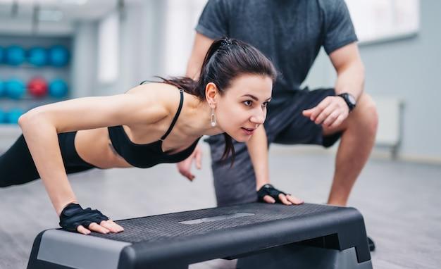Sportieve donkerharige vrouw doet push-ups van de plastic standaard en een trainer in sportclub.
