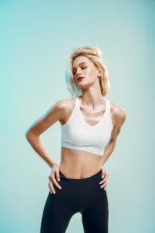 Sportieve en mooie jonge vrouw in witte top en zwarte legging die de ogen gesloten houdt terwijl
