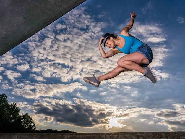 Sportieve europese vrouw die in de lucht springt op een bewolkte hemelachtergrond