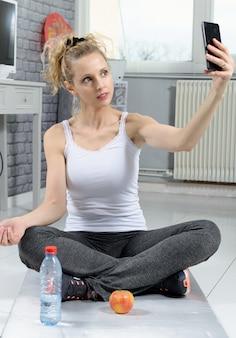 Sportieve fit fitness vrouw selfie thuis maken