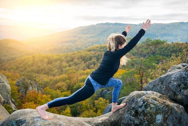 Sportieve fit vrouw is het beoefenen van yoga op de top van de berg