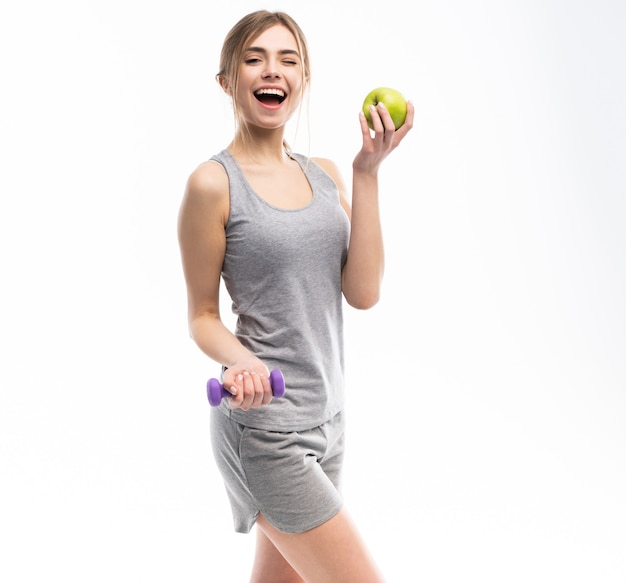 Sportieve fit vrouw met halters gewichten in de ene en appelfruit in een andere hand